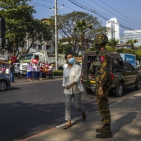 A soldier stands by during a protest in Yangon, Myanmar, in February. Four officers spoke about life in the feared Tatmadaw, which has turned its guns on civilians again.   | THE NEW YORK TIMES