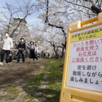 A sign asking people to take steps to prevent the spread of COVID-19 is set up at Osaka Castle Park in the city of Osaka on Saturday. | KYODO