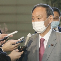 Prime Minister Yoshihide Suga speaks to reporters after meeting with his predecessor, Shinzo Abe, at the Prime Minister's Office on Monday. | KYODO
