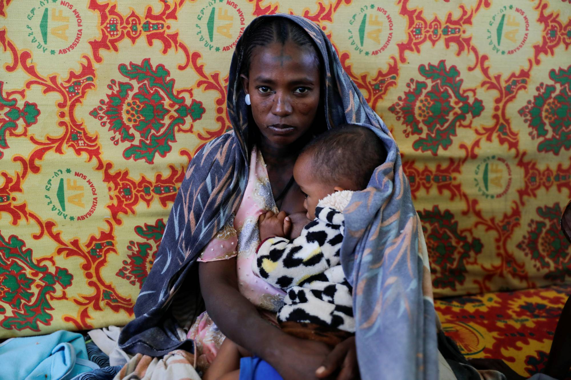 A woman holds an infant at the Adiha secondary school, which was turned into a temporary shelter for people displaced by conflict, in the city of Mekelle, in Ethiopia's Tigray region, on March 12. | REUTERS