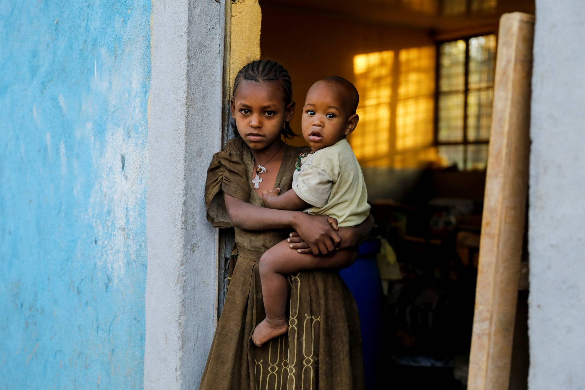 Asmara, 11, holds her 1-year-old brother, Barakat, at the doorway to a classroom now used as their living space in the town of Shire. | REUTERS