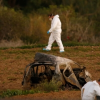 Forensic experts work after a powerful bomb blew up a car and killed investigative journalist Daphne Caruana Galizia in Bidnija, Malta, in October 2017. | REUTERS