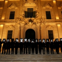 Activists from Occupy Justice Malta hold up placards reading 'Who Owns 17 Black?' in reference to revelations by the Daphne Project, outside the office of then-Prime Minister Joseph Muscat at Auberge de Castille in Valletta, Malta, in May 2018.   | REUTERS
