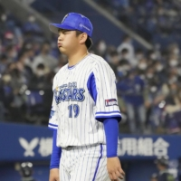 BayStars reliever Yasuaki Yamasaki walks back to the bench after the eighth inning against the Swallows on Tuesday at Yokohama Stadium. | KYODO