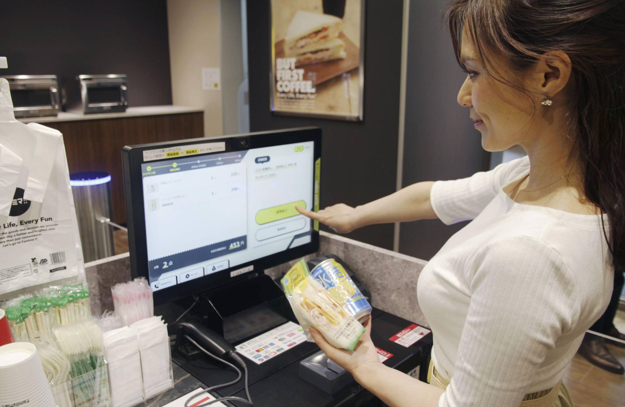 A demonstration is held Tuesday in Tokyo at a FamilyMart Co. store with an unmanned payment system. | KYODO