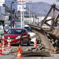 A gate of a house collapses on a street in Koori, Fukushima Prefecture, after a major earthquake struck northeastern Japan late on Feb. 13. | KYODO