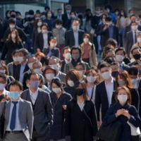 Commuters walk near Shinjuku Station in Tokyo on Monday, the second day of a new coronavirus state of emergency covering Tokyo, Osaka, Kyoto and Hyogo prefectures. | AFP-JIJI