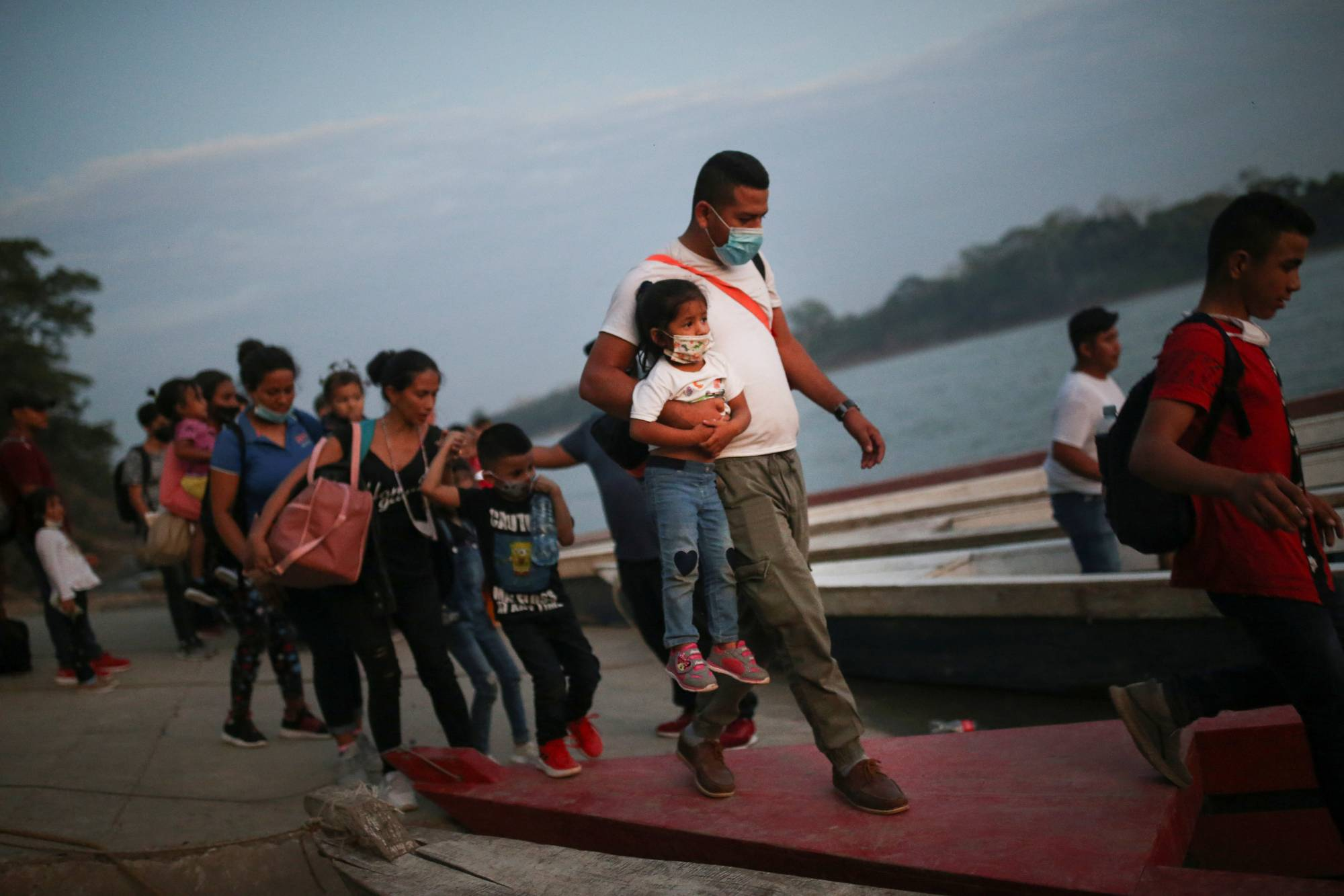 Honduran migrant families trying to reach the U.S. get on boats to cross the Usumacinta river, at La Tecnica in the Lacandon jungle of Guatemala on March 6.  | REUTERS