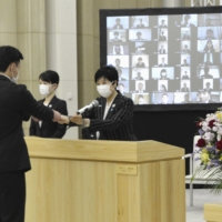 Tokyo Gov. Yuriko Koike hands out a letter of appointment to a new recruit at a welcome ceremony for new employees at the metropolitan government office on Thursday. | KYODO