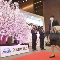 A new recruit arrives for her first day of work at Itochu Corp. as Chairman and CEO Masahiro Okafuji and others welcome her at the entrance of the company's head office in Tokyo. | KYODO