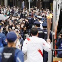 Crowds gather to watch a Tokyo Olympic torchbearer run through the city of Tochigi on Sunday. | KYODO