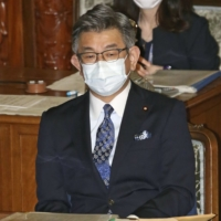 Communications minister Ryota Takeda attends the Lower House plenary session on Thursday, where a no-confidence motion against him was rejected. | KYODO