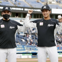 Marines pitcher Fumiya Motomae (right) celebrates with manager Tadahito Iguchi after recording the first win of his career in Chiba on Thursday.  | KYODO