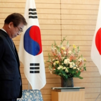 Suh Hoon, South Korea's National Intelligence Service chief at the time, waits for Prime Minister Shinzo Abe to arrive prior to their meeting in Tokyo in March 2018.   POOL / VIA REUTERS