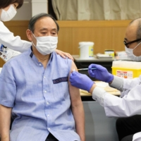 Prime Minister Yoshihide Suga receives his first dose of the Pfizer-BioNtech COVID-19 vaccine at the National Center for Global Health and Medicine in Tokyo on March 16.   KYODO