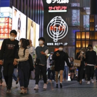 People walk in the Minami district of Osaka on Thursday. | KYODO