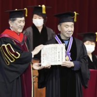 Haruki Murakami (right) receives an award for his distinguished service in the arts from Waseda University President Aiji Tanaka, at the university in Tokyo on Thursday. | KYODO