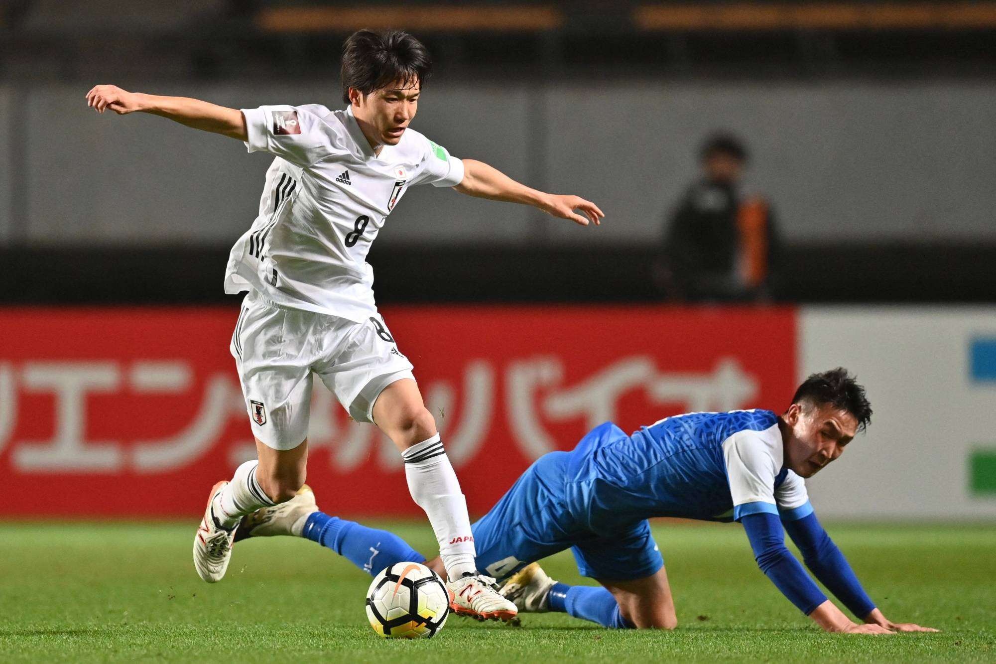 Sho Inagaki (left) contends for the ball with Mongolia's Amaraa Dulguun during a World Cup qualifier in Chiba on Tuesday. | AFP-JIJI
