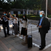 Journalists take pictures and wait to be tested for COVID-19 before attending a news conference in Beijing in May 2020. | REUTERS