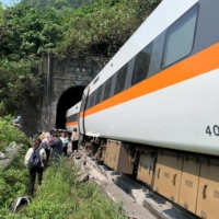 People walk next to a train that derailed in a tunnel north of Hualien, Taiwan, on Friday.  | TAIWAN'S NATIONAL FIRE AGENCY / VIA REUTERS