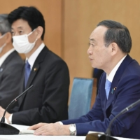 Prime Minister Yoshihide Suga (right) announces applying new COVID-19 countermeasures to Osaka, Hyogo and Miyagi prefectures in a task force meeting at the Prime Minister's Office on Thursday. | KYODO