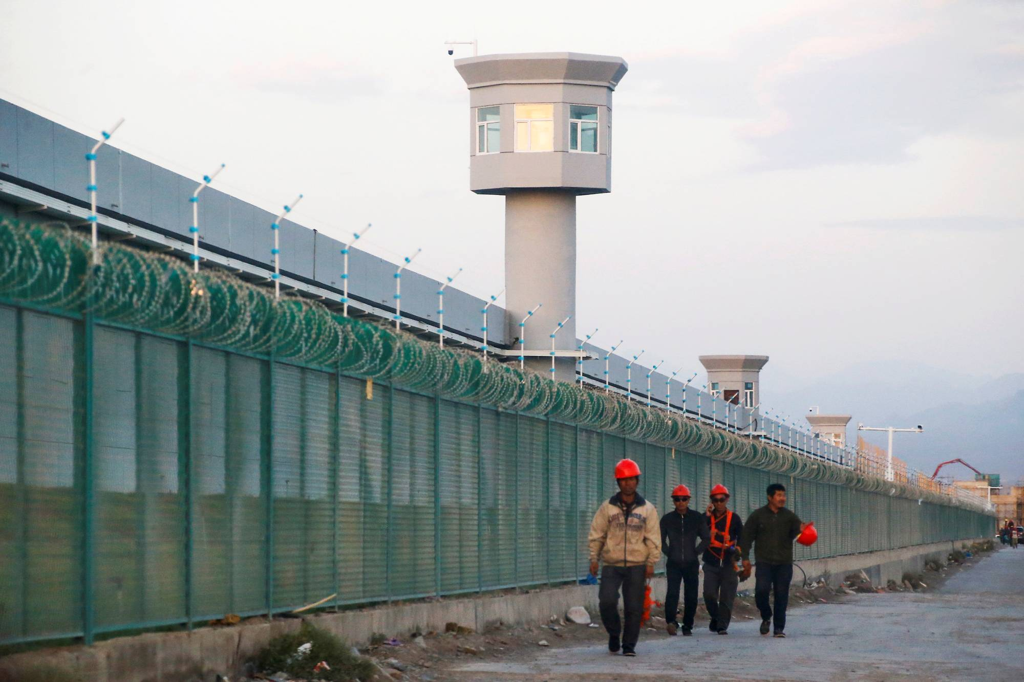 Workers walk by the perimeter fence of what is officially known as a vocational skills education center in Dabancheng, in China's Xinjiang region, in September 2018. | REUTERS