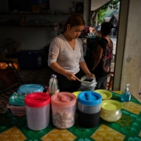 A Karen migrant living in Thailand prepares food at her shop in Mae Sam Laep, near the border with Myanmar. Annual cross-border trade stood at more than $9 billion in 2019 and many Thai businesses rely on Myanmar migrant workers — who officially number 1.6 million. | AFP-JIJI