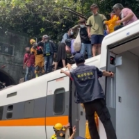 Rescue team members help stranded passengers down from the roof of a train that derailed in a tunnel north of Hualien, Taiwan, on Friday in this image taken from video posted to Facebook.  | @HUALIENFASTNEWS / VIA REUTERS