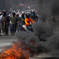 Demonstrators march near a burning road block during a protest against the government of President Jovenel Moise, in Port-au-Prince, Haiti, on March 28.  | REUTERS