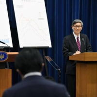 Prime Minister Yoshihide Suga (left) speaks at a news conference along with Shigeru Omi, head of the government's COVID-19 subcommittee, on March 18 at the Prime Minister's Office. | KYODO