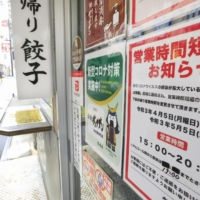 A notice for shortened business hours is put up at a restaurant in Sendai on Sunday. | KYODO