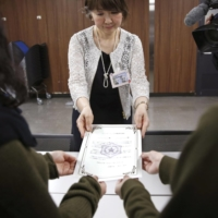 A Sapporo city official (back) gives a female couple a receipt certifying that the city government has accepted their 'partnership vow' at the municipal office in June 2017.  | KYODO