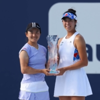 Shuko Aoyama (left) and Ena Shibahara pose with the Butch Bucholz Trophy after winning the women's doubles final at the Miami Open on Sunday. | USA TODAY / VIA REUTERS
