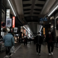 Pedestrians wearing protective masks walk through a shopping district in Kawasaki in February. | BLOOMBERG