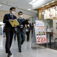 Osaka prefectural and city officials patrol restaurants in Osaka on Monday. | KYODO