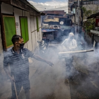 A worker disinfects a street in Manila on March 26. | BLOOMBERG