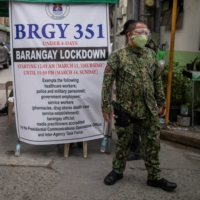 A police officer mans a checkpoint in a village under lockdown amid rising COVID-19 infections in Manila on March 12. | REUTERS