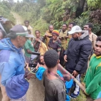Janius Bagau, on a makeshift stretcher, is carried by his two brothers, Soni (in a black T-shirt with his back to the camera) and Yustinus (in a green and yellow tracksuit top), and others on the way to a health clinic in Intan Jaya regency, Papua, Indonesia, Feb. 15. | VIA REUTERS
