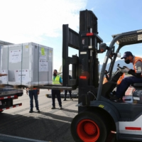 Workers load a container holding doses of the AstraZeneca vaccine, which arrived through the COVAX program, in Alajuela, on the outskirts of San Jose, Costa Rica, on Wednesday.  | REUTERS