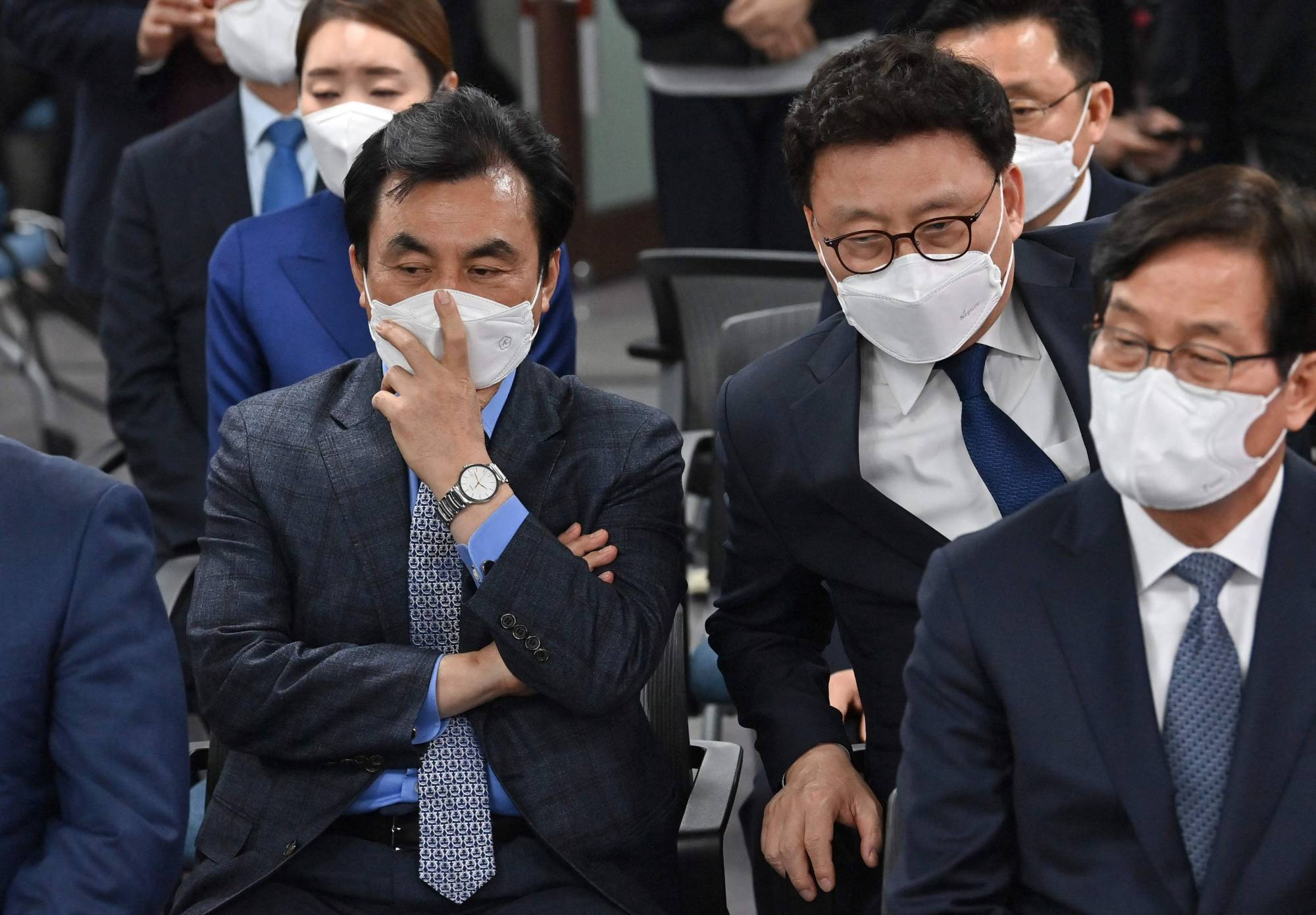 Members of South Korea's ruling Democratic Party watch screens showing the result of exit polls of the Seoul mayoral by-election at the party headquarters in Seoul on Wednesday. | AFP-JIJI