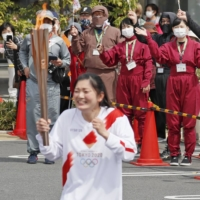 Mio Watanabe, who performs in a ninja show, leads the Olympic torch relay in Iga, Mie Prefecture, on Thursday. | KYODO