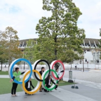 People pose with the Olympic rings near National Stadium on Tuesday. | YUKIHITO TAGUCHI / USA TODAY / VIA REUTERS
