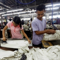 Workers iron and arrange clothing at a garment factory in the Hlaing Taryar industrial zone in Yangon, Myanmar, in 2010. | REUTERS
