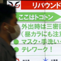A screen at a street in Tokyo's Shinjuku district on Thursday asks people to take measures to prevent a rebound in the number of COVID-19 infections. | KYODO
