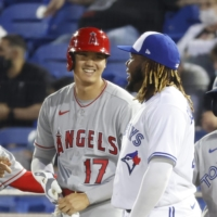 The Angels' Shohei Ohtani talks with Blue Jays first basemen Vladimir Guerrero Jr. after a single during the seventh inning of their game on Thursday. | USA TODAY / VIA REUTERS
