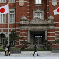 People walk past Tokyo Station on Thursday. | REUTERS