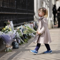 A girl adds to floral tributes against the railings at the front of Buckingham Palace in central London on Friday.  | AFP-JIJI