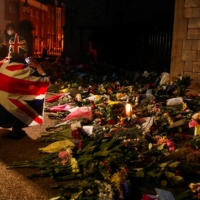 A mourner draped in a British Union Jack flag takes pictures of the flowers placed outside Windsor Castle, near London, on Friday.  | REUTERS