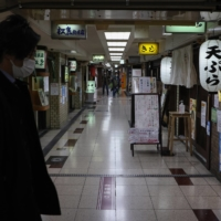 A pedestrian walks past bars along a covered pathway in the Umeda district of Osaka on Friday. | BLOOMBERG