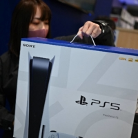 An employee prepares the new Sony PlayStation 5 gaming console for a customer on the first day of its launch at an electronics shop in Kawasaki in November. | AFP-JIJI